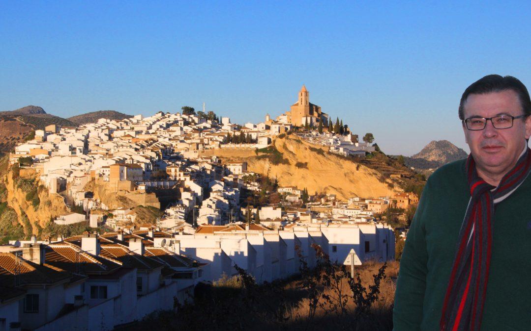 El Alcalde de Iznájar, Lope Ruiz, con el pueblo al fondo